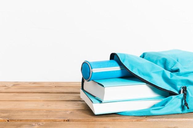 Blauw boeken en potlodengeval in het openen van schooltas op houten lijst Gratis Foto