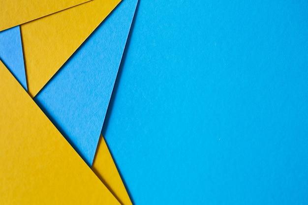 Blauw en geel, kleur papier geometrische plat lag achtergrond. Gratis Foto