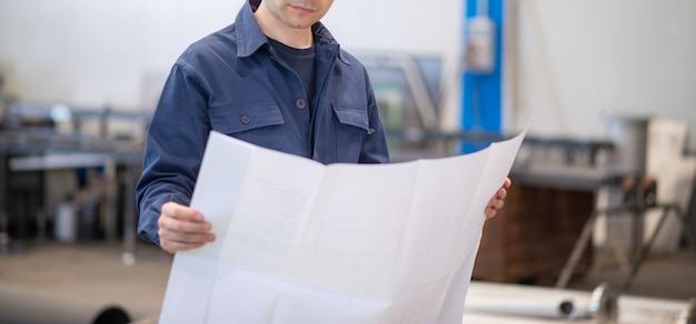Blauw geklede ingenieur die een bluepringtekening leest in een industriële faciliteit. gezicht niet zichtbaar Premium Foto
