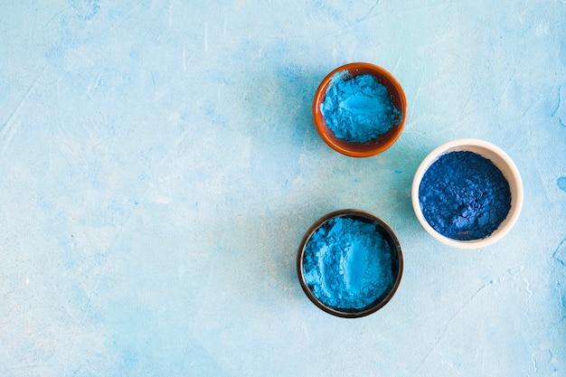 Blauw holi-kleurenpoeder in het verschillende type kommen op beton geschilderde achtergrond Gratis Foto