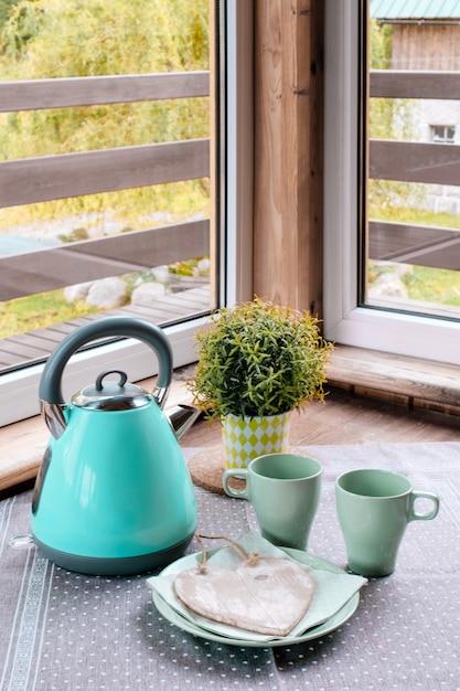 Blauw ijzer ketel groene tafel cup blauw groen ontbijt mand hart venster Premium Foto