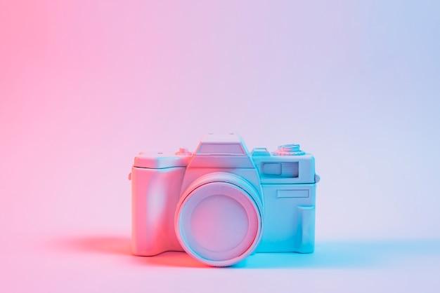 Blauw licht over een oude vintage camera over roze oppervlak geschilderd Gratis Foto
