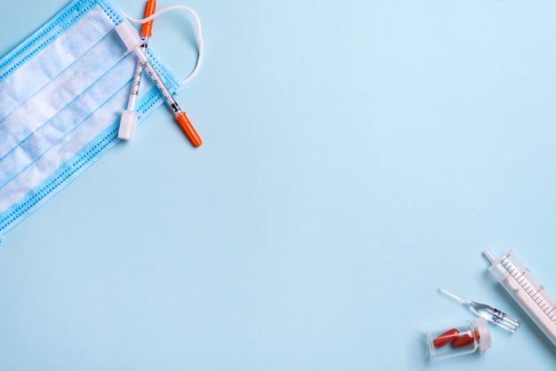 Blauw medisch masker en wegwerpspuit. medische benodigdheden. kopieer ruimte Premium Foto