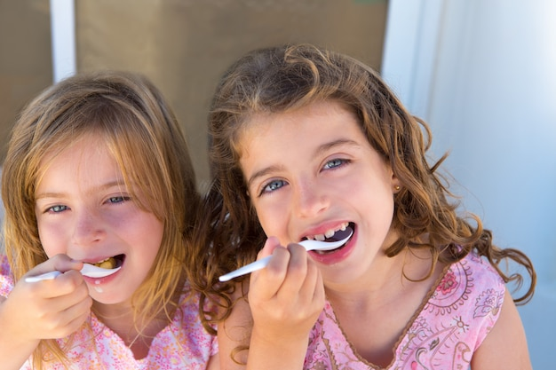 Blauw ogenjonge zustermeisje die ontbijt eten Premium Foto