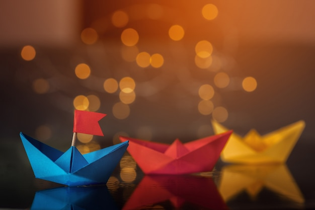 Blauw papieren schip met vlag onder andere schepen. Premium Foto