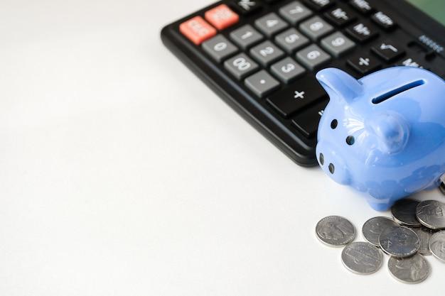 Blauw spaarvarken, rekenmachine en munten Premium Foto