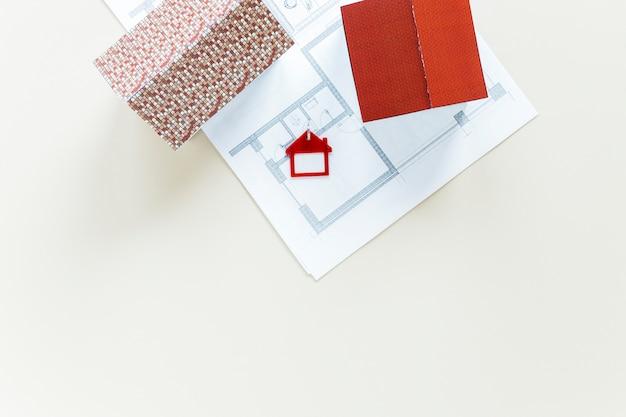 Blauwdruk en huismodel met sleutelhanger op witte achtergrond wordt geïsoleerd die Gratis Foto