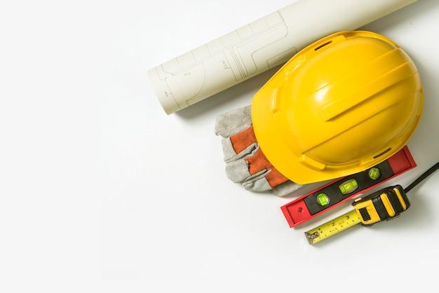 Blauwdruk gele veiligheidshelm voor bouw en hulpmiddelen op witte achtergrond. Premium Foto