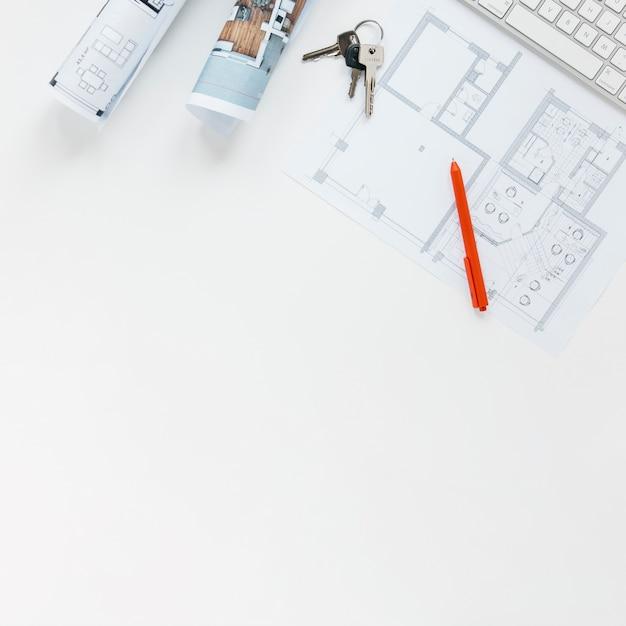 Blauwdruk met sleutels en rode pen die op witte achtergrond wordt geïsoleerd Gratis Foto