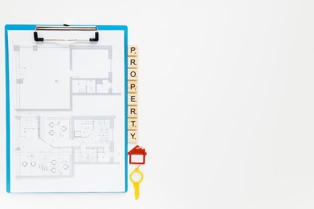 Blauwdrukklembord met bezitsblokken en huissleutel op witte achtergrond Gratis Foto