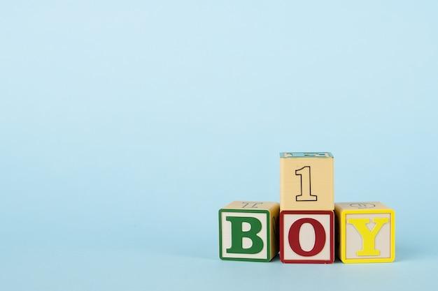 Blauwe achtergrond met gekleurde kubussen met letters boy en nummer Premium Foto