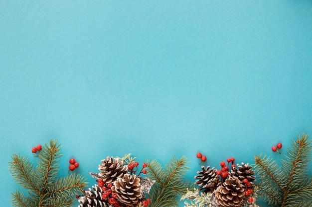 Blauwe achtergrond met pijnboombladeren en kegels Gratis Foto