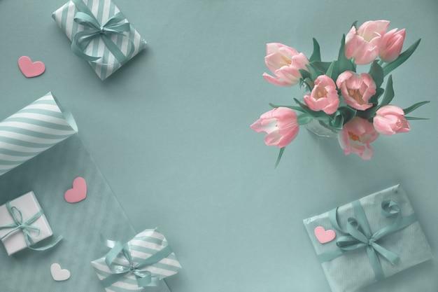 Blauwe achtergrond met roze tulpen, gestreept inpakpapier en geschenkdozen Premium Foto