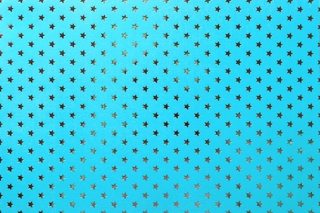 Blauwe achtergrond van metaalfoliepapier met een zilveren sterrenpatroon Premium Foto