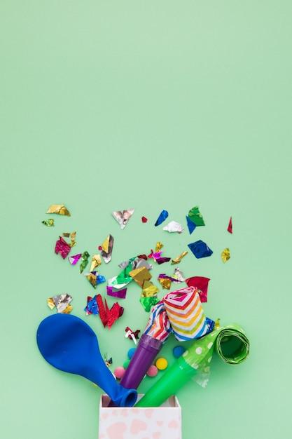 Blauwe ballon; confetti en hoornblazers die uit de doos op groene achtergrond komen Gratis Foto