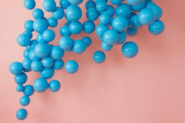 Blauwe ballonnen, blauwe bubbels op roze achtergrond. moderne, punchy pastelkleuren Gratis Foto