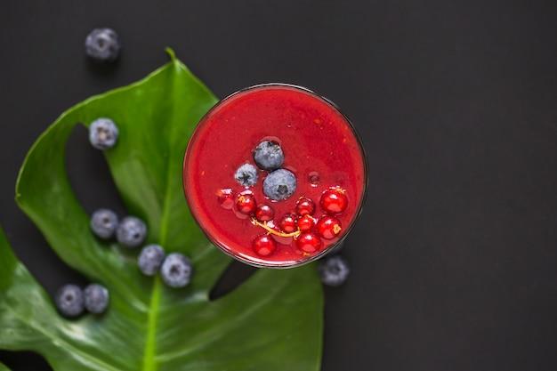 Blauwe bessen op smoothie en groen blad tegen zwarte achtergrond Gratis Foto