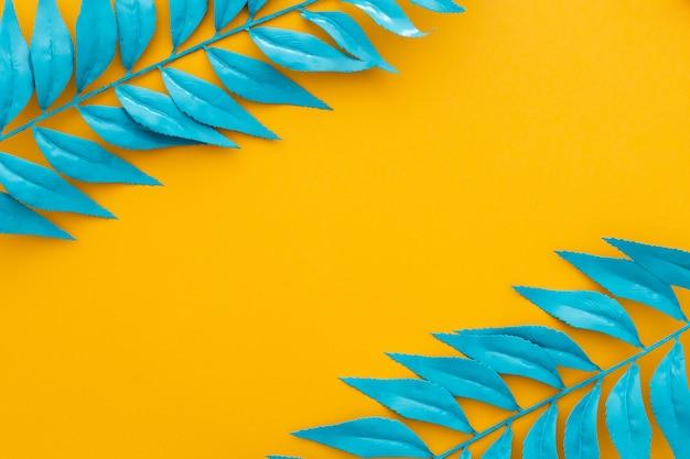 Blauwe bladeren op gele achtergrond Gratis Foto
