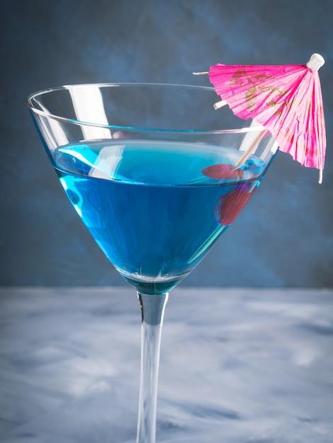 Blauwe cocktail in martini-glas met paraplu Premium Foto