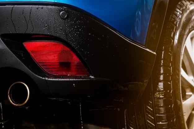 Blauwe compacte suv-auto met sportontwerp wast met water. auto zorg service bedrijfsconcept. auto bedekt met druppels water na reiniging met water en schuimspray. auto-industrie concept Premium Foto