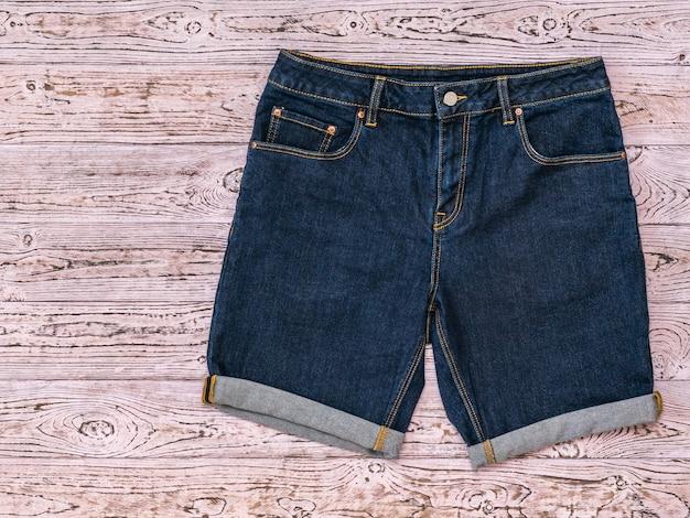 Blauwe denim short op een getint roze houten oppervlak Premium Foto
