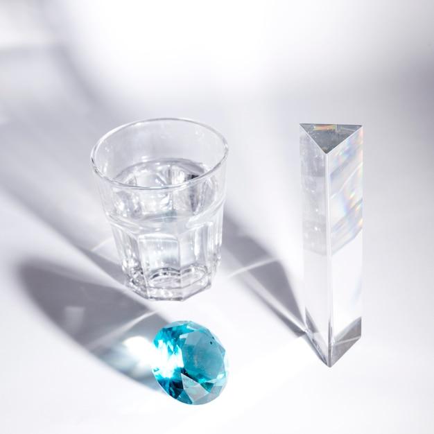 Blauwe diamant; lang kristal en glas water met schaduw op witte achtergrond Gratis Foto