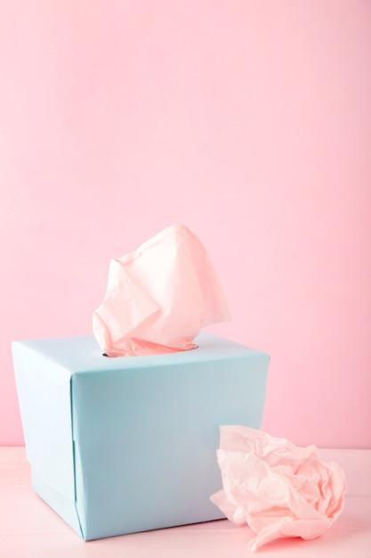 Blauwe doos met papieren zakdoekjes en gebruikte verfrommelde servetten Premium Foto