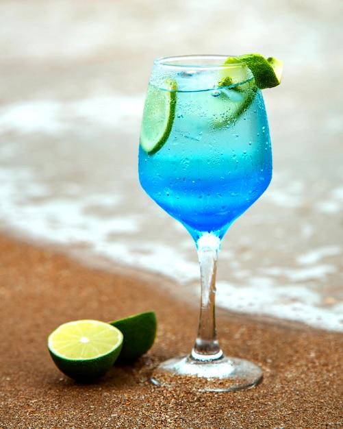 Blauwe drank met limoen op zee Gratis Foto