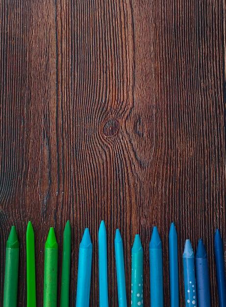 Blauwe en groene kleurpotloden in rij over houten lijst worden geschikt die Gratis Foto