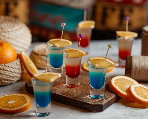 Blauwe en rode alcoholische dranken met sinaasappelplakken. Gratis Foto
