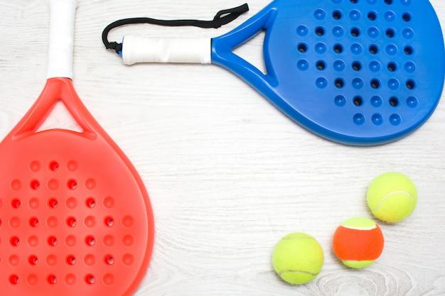 Blauwe en rode peddel tennisrackets en bal op witte houten tafelblad weergave Premium Foto