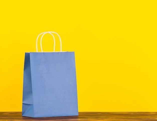 Blauwe enkele papieren zak op houten oppervlak met gele achtergrond Gratis Foto