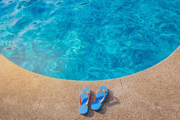 Blauwe flip-flops dichtbij het zwembad Gratis Foto