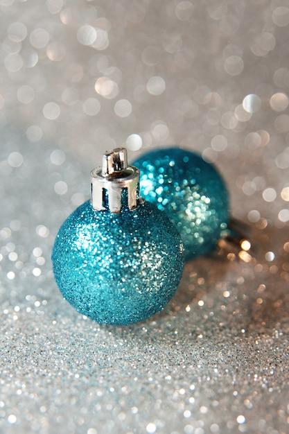 Blauwe fonkelende kerstballen op zilver glitter achtergrond. nieuwjaar, macrofoto Premium Foto