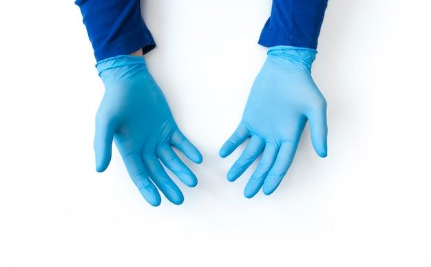 Blauwe gehandschoende handen sluiten omhoog op witte achtergrond. bel voor handdesinfectie. stop coronavirus concept Premium Foto