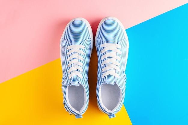 Blauwe gestreepte vrouwelijke sneakers op een kleurrijke achtergrond bovenaanzicht. plat leggen minimale achtergrond Premium Foto