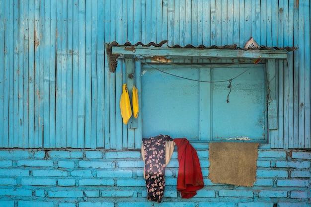 Blauwe gevel van een oud houten gebouw in de voorsteden met kleren opgehangen aan het raam Gratis Foto