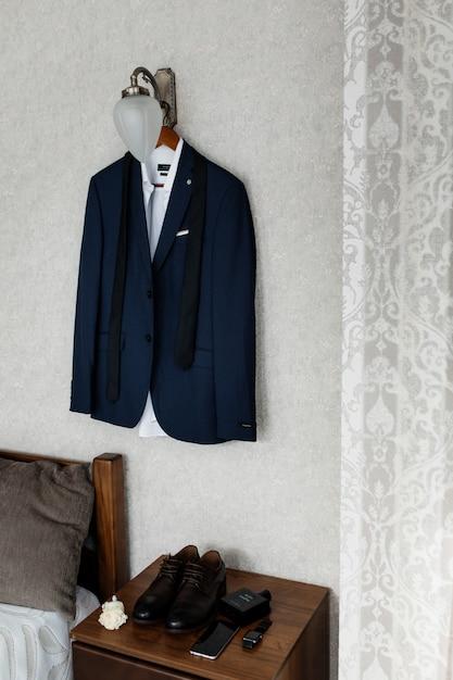 Blauwe huwelijkskledij voor een bruidegom die op de muur hangt Gratis Foto