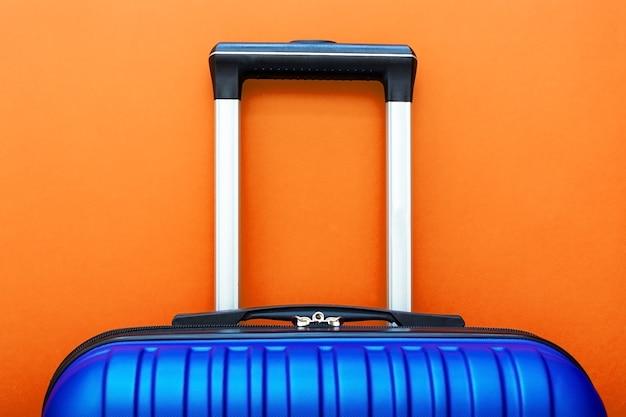 Blauwe koffer op oranje achtergrond kopie ruimte voor tekst. reis concept. Premium Foto