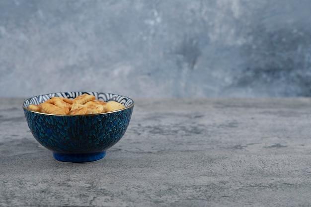 Blauwe kom vol met verschillende gezouten crackers op marmeren achtergrond. Gratis Foto