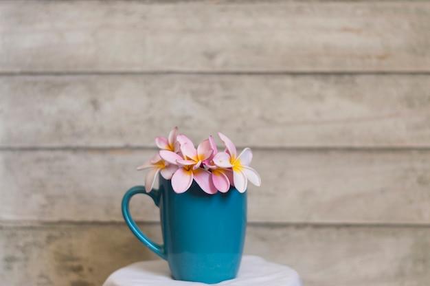 Blauwe kop met bloemen en houten achtergrond Gratis Foto