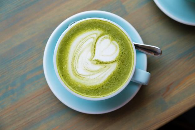 Blauwe kop met matcha latte op een houten tafel. Premium Foto
