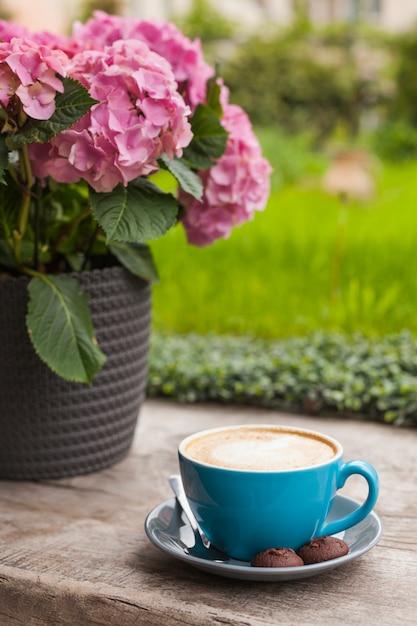 Blauwe kop van lattekoffie met koekjes op houten oppervlakte dichtbij roze bloempot Gratis Foto
