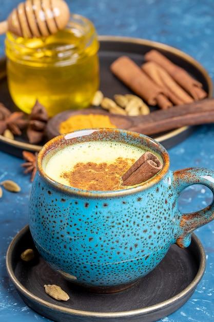 Blauwe kop van traditionele indiase ayurvedische gouden kurkuma latte melk met ingrediënten op blauwe achtergrond. selectieve aandacht. Premium Foto
