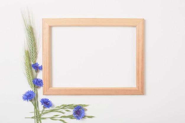 Blauwe korenbloemen en granen met houten frame op witte ondergrond Premium Foto