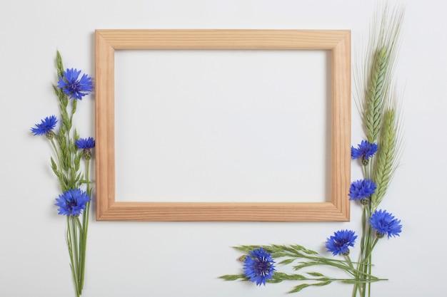 Blauwe korenbloemen en granen met houten frame Premium Foto