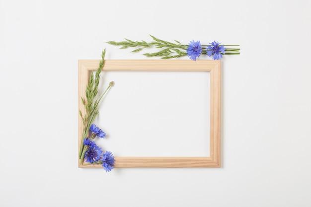 Blauwe korenbloemen en houten frame op witte ondergrond Premium Foto