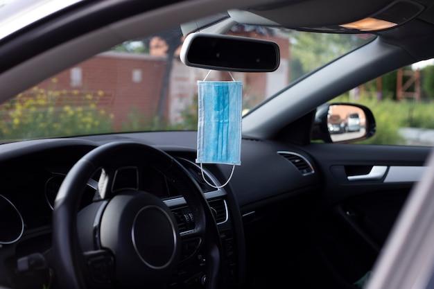 Blauwe medische bescherming masker opknoping in de achteruitkijkspiegel. beschermingsconcept tegen bacteriën en virussen. covid-19 Premium Foto