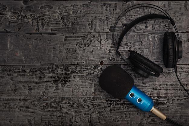 Blauwe microfoon met zwarte draad en zwarte koptelefoon op zwarte houten tafel. Premium Foto
