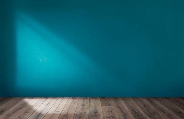 Blauwe muur in een lege ruimte met houten vloer Gratis Foto